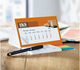 Calendario personalizado con bloc de notas adhesivas colocado en la mesa de trabajo