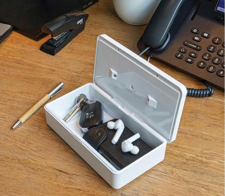 esterilizador UV-C en la mesa de trabajo con llaves y auriculares en el interior