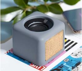 altavoz bluetooth de cemento de piedra caliza y corcho en una mesa de trabajo