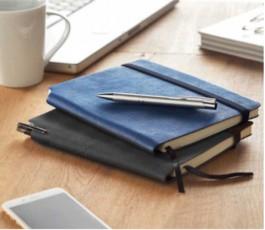 libreta tipo moleskine de tapa blanda de color azul con boligrafo encima de la mesa