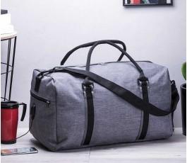 bolsa de viaje modelo A6043 color gris y detalles de color negro encima de una mesa